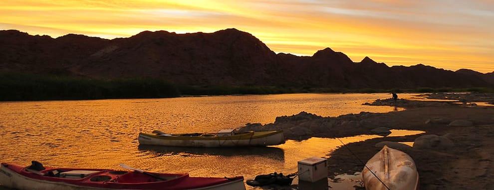 Coucher du soleil sur la rivière orange et ses bateaux en Afrique du Sud